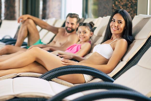 Glückliche familie im resort. hübscher vater, schöne mutter und diese kleine süße tochter liegen auf den sonnenliegen in einem großen wellnesscenter mit pool. entspannen sie sich im urlaub
