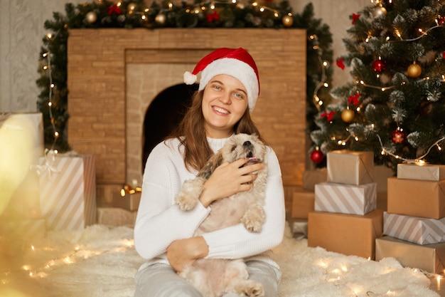 Glückliche familie im roten hut und im weißen lässigen pullover mit hund, der nahe weihnachtsbaum sitzt, geschenkboxen und kamin, fröhliches mädchen mit ihrem haustier, welpe beißt besitzerfinger.
