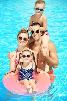 Glückliche familie im schwimmbad im wasserpark
