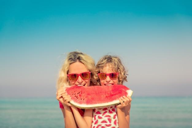 Glückliche familie im sommerurlaub menschen essen wassermelone am strand gesundes lebensstilkonzept
