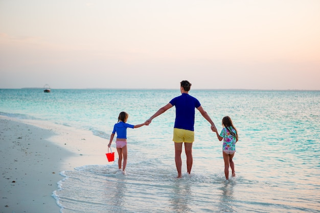 Glückliche familie im sonnenuntergang am strand