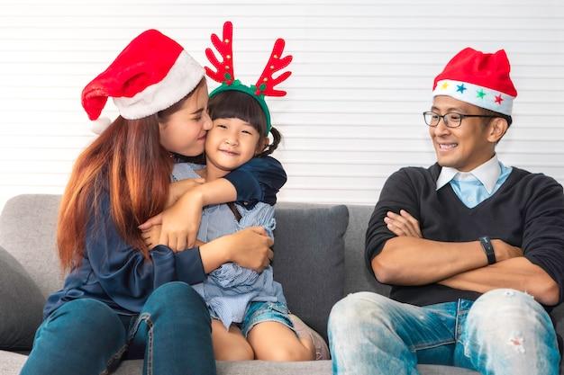 Glückliche familie im urlaub und weihnachten, elternteil und tochter küssen und lächeln.