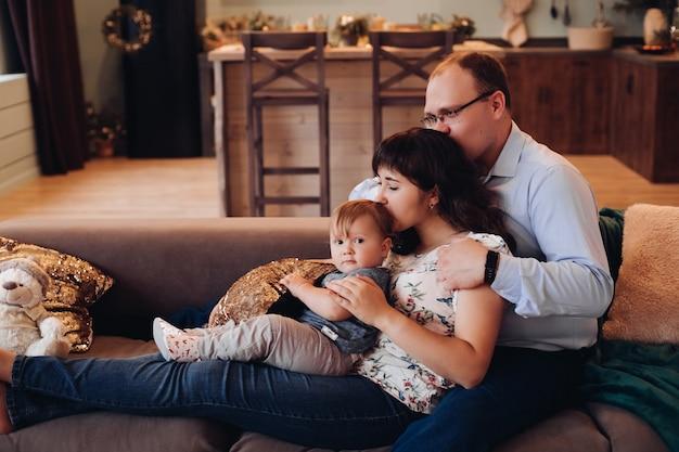 Glückliche familie im weihnachtlich dekorierten wohnzimmer.