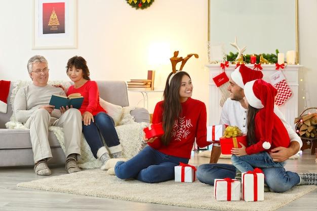 Glückliche familie im weihnachtlich dekorierten wohnzimmer Premium Fotos