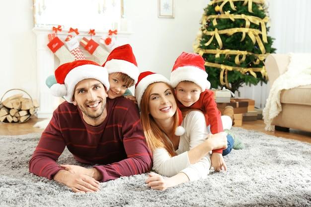 Glückliche familie im weihnachtlich dekorierten wohnzimmer