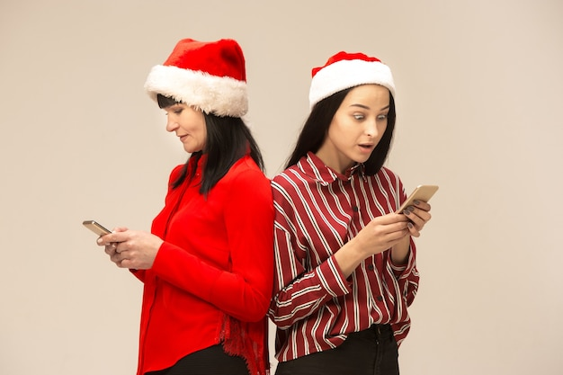 Glückliche familie im weihnachtspullover, der mit handys aufwirft. liebe umarmungen genießen, urlaub menschen. mutter und tochter auf grauem hintergrund im studio