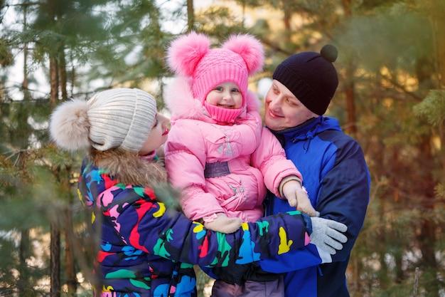Glückliche familie im winterwald. im winter zeit im freien verbringen