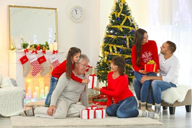 Glückliche familie im wohnzimmer, die sich gegenseitig weihnachtsgeschenke macht presents