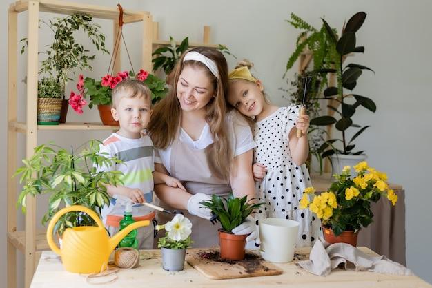 Glückliche familie in der fastenpflanze oder verpflanzung von zimmerblumen kleiner helfer bei der hausarbeit im garten