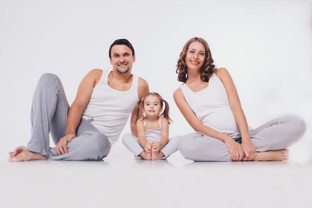 Glückliche familie in der freizeitgymnastik beschäftigt. ein mann, eine schwangere frau und ein kleines mädchen sitzen auf dem boden. isoliert
