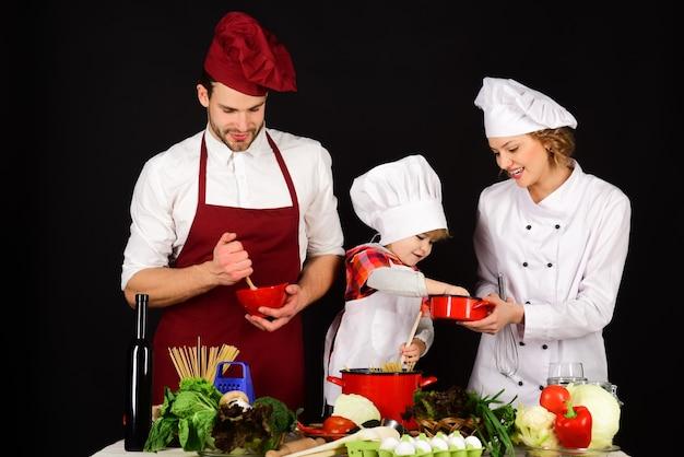 Glückliche familie in der küche. gesundes essen zu hause. konzept der freundlichen familie. entzückendes lächelndes kind in kochmütze mit eltern. gemeinsam kochen. vorbereitung zum frühstück, abendessen, abendessen.