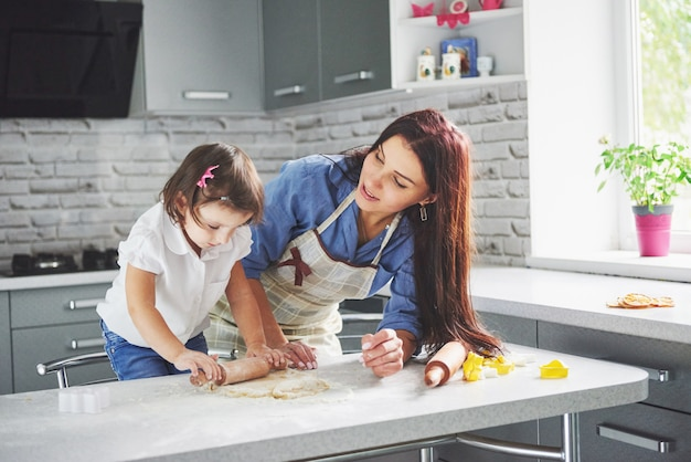 Glückliche familie in der küche. holiday food konzept. mutter und tochter bereiten den teig vor und backen kekse. glückliche familie bei der herstellung von keksen zu hause. hausgemachtes essen und kleiner helfer