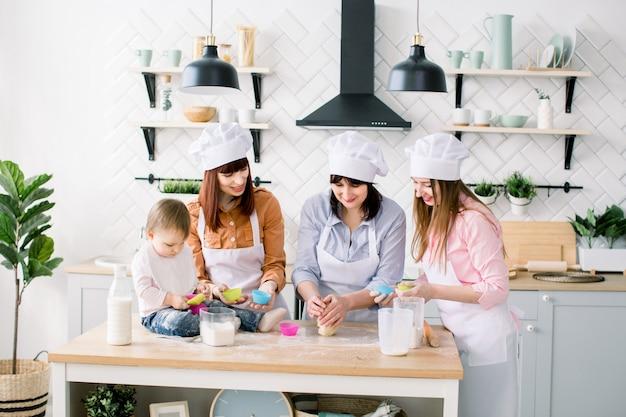 Glückliche familie in der küche. junge frau und ihre schwester, frau mittleren alters und kleine süße tochter kochen cupcakes für muttertag, lässige lifestyle-fotoserie im realen leben interieur