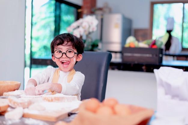 Glückliche familie in der küche. mutter, die sohn unterrichtet, um gesundes essen in den sommerferien zu kochen.