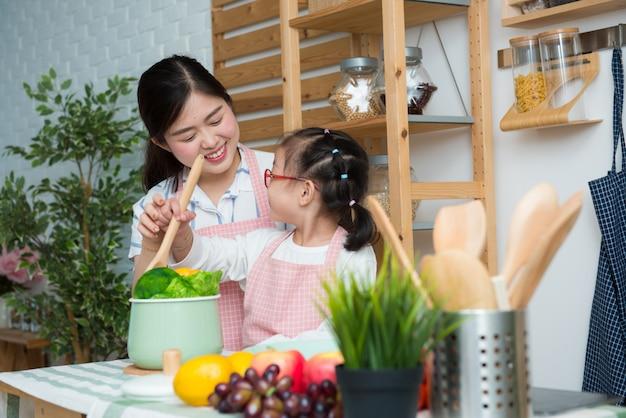 Glückliche familie in der küche. mutter und kind tochter das essen zubereiten.