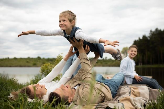 Glückliche familie in der natur voller schuss Kostenlose Fotos