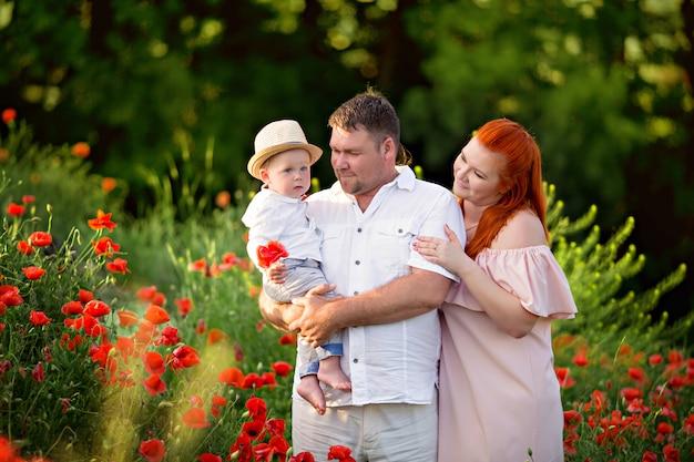 Glückliche familie in einem feld der blühenden mohnblumen