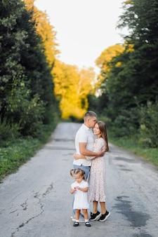 Glückliche familie in einem park im sommer herbst. mutter, vater und baby spielen in der natur in den strahlen des sonnenuntergangs
