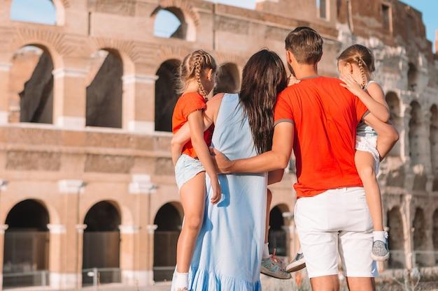 Glückliche familie in europa. eltern und kinder in rom über kolosseum