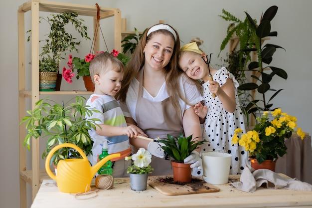 Glückliche familie in fastenpflanze oder verpflanzung von zimmerblumen kleiner helfer bei der hausarbeit