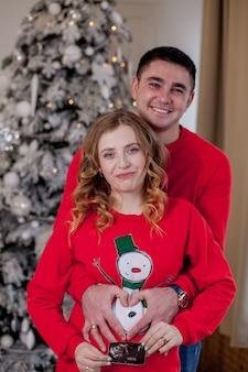 Glückliche familie in ihrem wohnzimmer nahe weihnachtsbaum