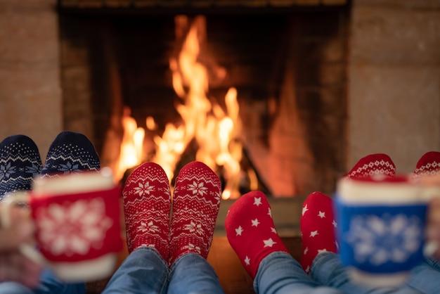 Glückliche familie in weihnachtssocken am kamin muttervater und kinder in der weihnachtszeit