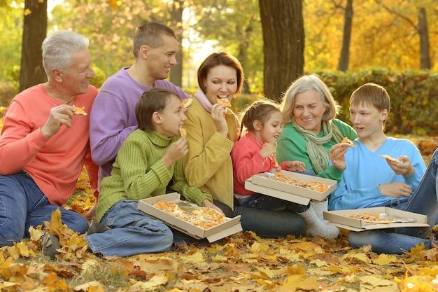Glückliche familie isst zusammen pizza im herbstpark