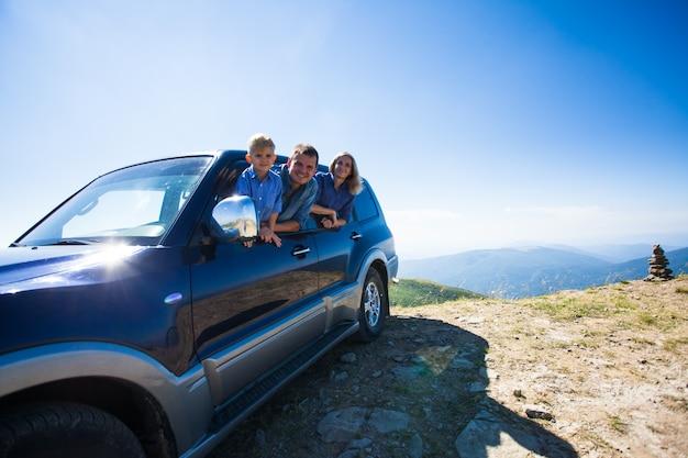 Glückliche familie, junger vater, mutter und sohn, die auf reisen aus dem auto schauen