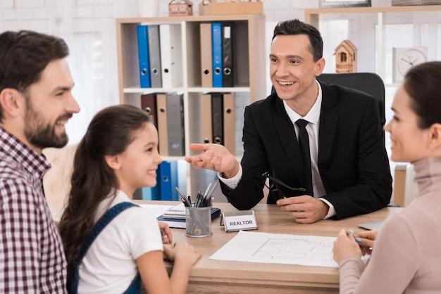 Glückliche familie kauft immobilien im büro des grundstücksmaklers.