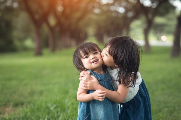 Glückliche familie. kleine mädchenschwestern, die draußen im sommer küssen und lachen