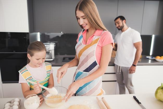 Glückliche familie kocht mit teig an der küche.