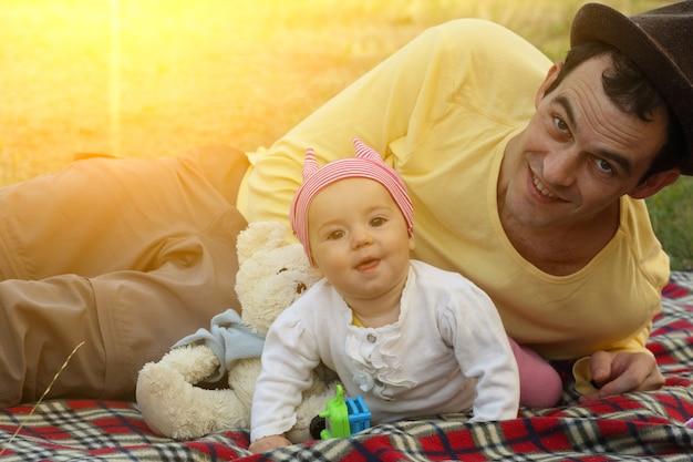 Glückliche familie - lächelnder vater und kleine tochter beim picknick im freien