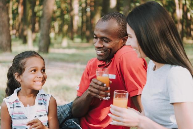Glückliche familie lächelt im wald und trinkt saft