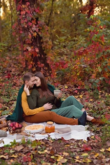 Glückliche familie, liebhaber, ehemann und ehefrau, die auf einem senna-picknick mit kürbis, äpfeln, tee umarmen