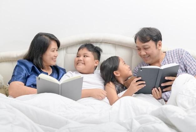 Glückliche familie liest eine geschichte auf dem bett im schlafzimmer,