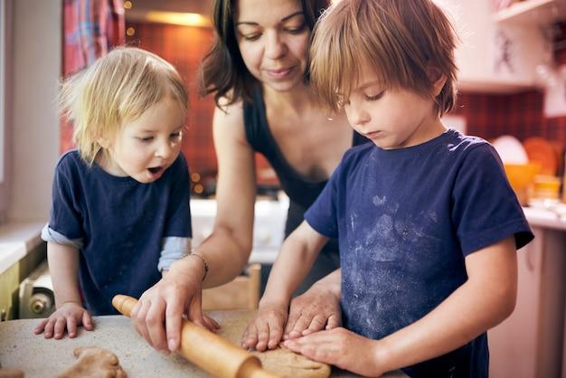 Glückliche familie lustige jungen und ihre mutter bereiten den teig vor