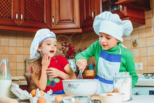 Glückliche familie lustige kinder bereiten den teig vor, backen kekse in der küche