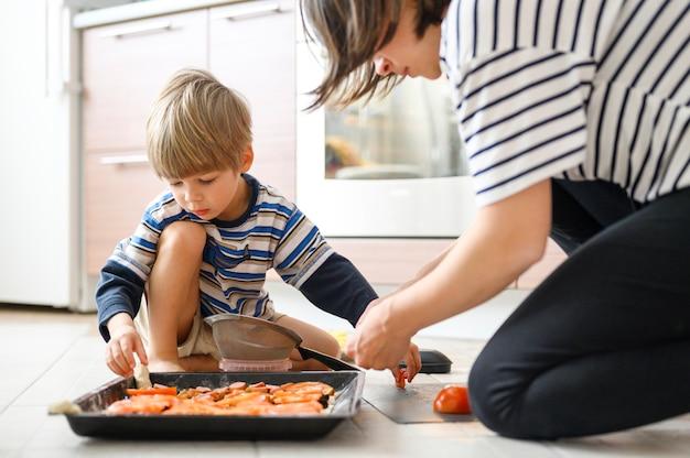 Glückliche familie machen essen zu hause. mutter zusammen ihr vierjähriges kind sohn kleinkind kochen pizza in der küche.