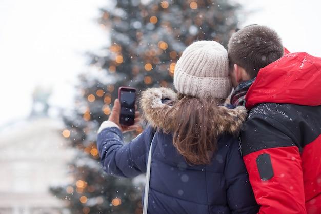 Glückliche familie macht ein foto nahe dem weihnachtsbaum