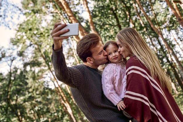 Glückliche familie macht selfie mit dem smartphone im wald