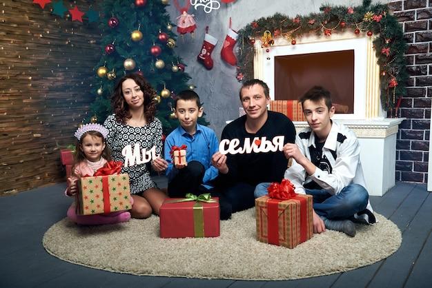 Glückliche familie: mama, papa und drei kinder am kamin für die winterferien. heiligabend und silvester.
