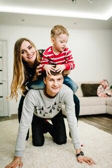 Glückliche familie: mama, papa und kleiner sohn in weihnachtsmann-pullovern spielen auf dem boden. liebe umarmungen genießen, urlaub menschen. zusammengehörigkeitskonzept.