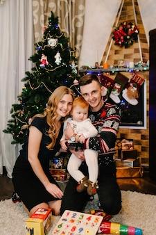 Glückliche familie: mama, papa und tochter in der nähe des weihnachtsbaumes mit geschenken und kamin. neujahrskonzept. fröhliche weihnachten.