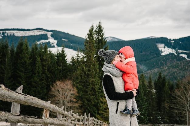 Glückliche familie: mama und mädchen haben spaß und spielen im verschneiten winter, spazieren in den bergen, in der natur. mutter und kinder tochter genießen reise. frost wintersaison.
