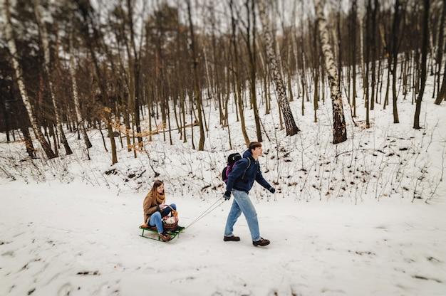Glückliche familie: mann tragen holzschlitten mit mädchen auf schlitten, der im wald draußen geht. wandern am ferienwochenende im winterpark.