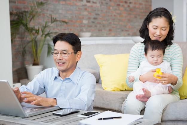 Glückliche familie mit babytochter im wohnzimmer, das rechnungen zählt