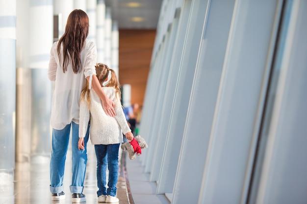 Glückliche familie mit bordkarte am flughafen, der den flug wartet