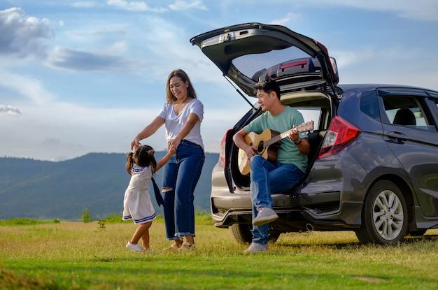 Glückliche familie mit dem auto auf dem land