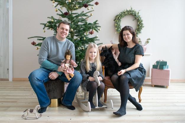 Glückliche familie mit dem hund, der kamera im raum mit cristmas baum- und des neuen jahresdekorationen lächelt und betrachtet