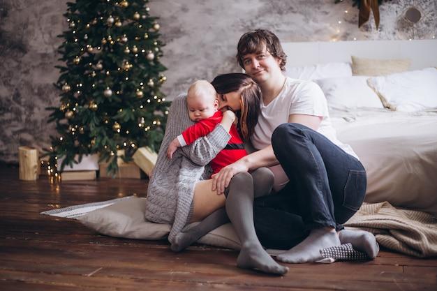 Glückliche familie mit dem kleinen kind, das zu hause nahe weihnachtsbaum sitzt
